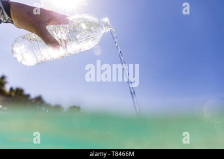 Woman pouring bottled water into sea - Stock Photo