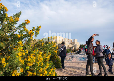 Athens, Greece - March 9, 2019: Tourists take selfies on Areopagus Hill against the Acropolis of Athens in the background - Stock Photo