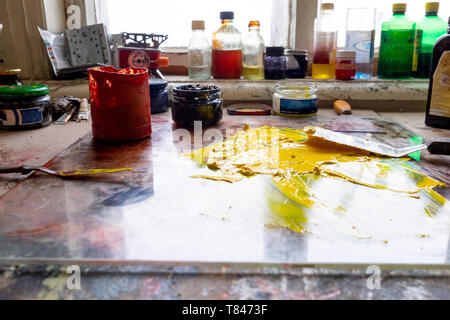 Spilt yellow paint on table - Stock Photo