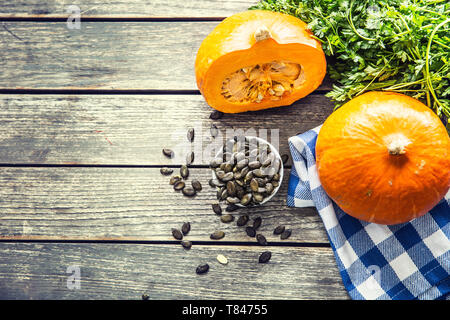 Roasted pumpkin seeds with raw pumpkins on wooden table - Stock Photo