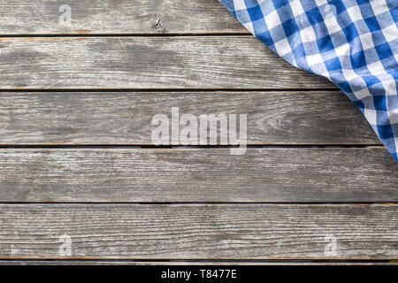 Blue white checketed tablecloth on wooden kitchen table - top of view - Stock Photo
