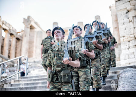 Greek soldiers march in formation while on patrol at the Acropolis of Athens. The Acropolis of Athens is an ancient citadel standing on a rocky outcro - Stock Photo