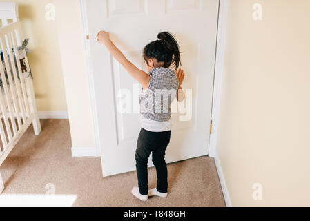 Girl opening nursery door, rear view - Stock Photo