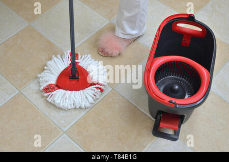 Mop and a bucket on a floor during a housework - Stock Photo