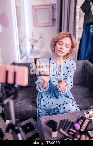 Woman with short hair cut recommending eye shadows palette - Stock Photo
