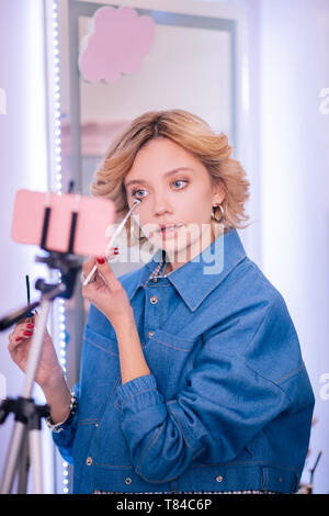 Blogger wearing denim jacket doing makeup and filming it - Stock Photo