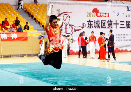 Beijing, China. 10th May, 2019. A student performs cudgel play during a Wushu (Chinese martial arts) competition in Ditan stadium, Beijing, captial of China, May 10, 2019. Credit: Zhou Liang/Xinhua/Alamy Live News - Stock Photo