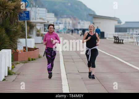 Hastings, East Sussex, UK. 11 May, 2019. UK Weather: Bright but cold morning in Hastings, East Sussex. Rain is expected for the afternoon, the temperature is not expected to exceed 10 degrees Celsius. A few people take to the seafront promenade, some walking, some jogging while the weather is clear. Two ladies jog along the seafront. © Paul Lawrenson 2019, Photo Credit: Paul Lawrenson/Alamy Live News - Stock Photo