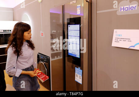Beijing, China. 10th May, 2019. A visitor looks at a smart fridge during China Brand Day 2019 at Shanghai Exhibition Center in Shanghai, east China, May 10, 2019. Credit: Fang Zhe/Xinhua/Alamy Live News - Stock Photo
