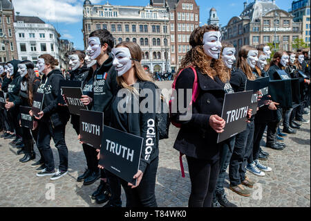 Amsterdam, Netherlands. 111th May 2019. Vegan activists seen wearing Guy Fawkes masks while holding placards during the demonstration. Hundreds of activists gathered at the Dam square in the center of Amsterdam to participate in The Cube of Truth. Anonymous for the Voiceless hosted a 24-hour Cube of Truth in Dam Square, Amsterdam. The Cube of Truth is a peaceful static demonstration similar to an art performance. This demonstration operates in a structured manner that triggers curiosity and interest from the public; the activists attempt to lead bystanders to a vegan conclusion through a combi - Stock Photo