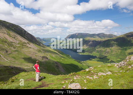 Lake District National Park, Cumbria, England. Girl admiring view over Buttermere and distant Crummock Water from the western slopes of Haystacks. - Stock Photo