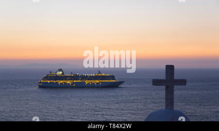 Mykonos Town, Mykonos, South Aegean, Greece. View across the Aegean Sea from hillside, dusk, illuminated cruise ship anchored offshore. - Stock Photo