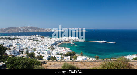 Mykonos Town, Mykonos, South Aegean, Greece. Panoramic view over the town and harbour from hillside. - Stock Photo
