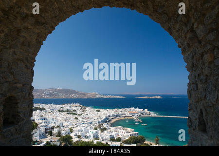 Mykonos Town, Mykonos, South Aegean, Greece. View over the town and harbour through stone archway in the castle ramparts. - Stock Photo