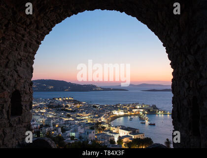 Mykonos Town, Mykonos, South Aegean, Greece. View over the illuminated town and harbour through stone archway in the castle ramparts, dusk. - Stock Photo