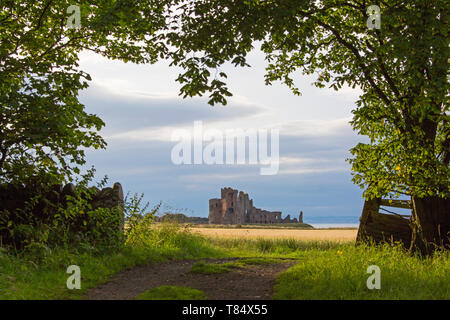 North Berwick, East Lothian, Scotland. View along path through gate to the ruins of Tantallon Castle, sunset. - Stock Photo