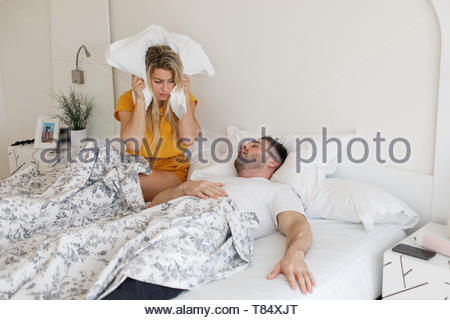 Woman covering her ears with the pillow because of the loud snoring of her partner. Bed couple relationship problems. - Stock Photo