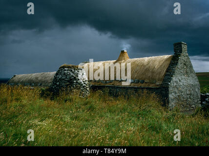 Shetland Croft House Museum, Boddam, Scotland, UK: rear view of restored C19th house (R) with corn drying kiln attached to the barn & stable (L). - Stock Photo