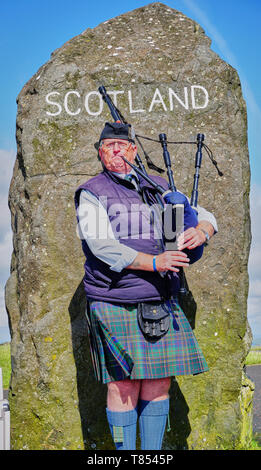 Male Scottish Bagpiper playing in front of border crossing market in Scotland - Stock Photo