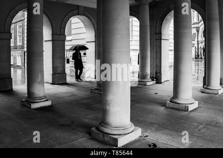 Temple, London, UK - February 8th, 2019 - a man with umbralla walks through collonnade on a windy day - Stock Photo