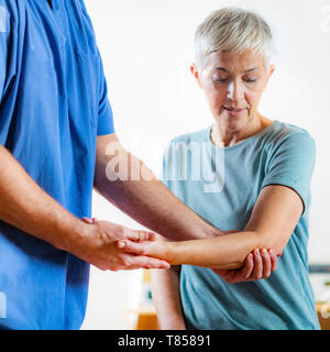 Physical therapist examining patient's elbow - Stock Photo