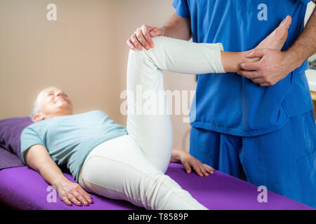 Physical therapist examining patient's leg - Stock Photo