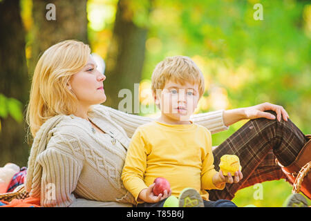 Mom and kid boy relaxing while hiking forest. Family picnic. Mother pretty woman and little son relaxing forest picnic. Good day for spring picnic in nature. Having snack during hike. Happy childhood. - Stock Photo