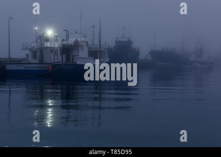 An evening fog rolls in from the Atlantic sea and blankets Hout Bay harbour in mist on the Cape Peninsula, near Cape Town in South Africa - Stock Photo
