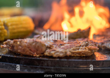 fresh raw steak with corn an a open fire grill - Stock Photo