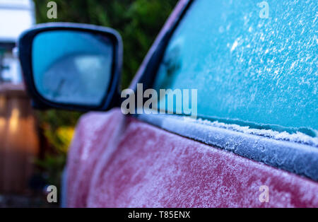 Purple car covered in frost on a very cold winter morning before scraping the ice off the windows and going to work in the depth of winter. - Stock Photo