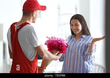 Young woman receiving beautiful flowers from delivery man - Stock Photo
