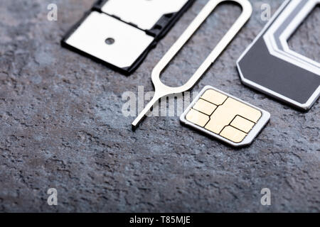 Nano Sim Card In The Card Adapter With Eject Pin On Concrete Surface - Stock Photo