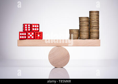 Red Dice Stack And Money Coins Balancing On A Seesaw - Stock Photo