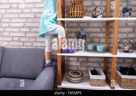Close-up Of Small Girl Trying To Climb On Shelf At Home