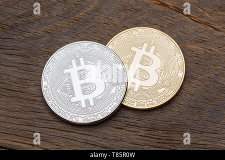 Silver and golden bitcoins on wooden background.  - Stock Photo