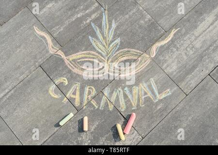 Text carnival and mask drawn in crayons on gray asphalt, top view - Stock Photo