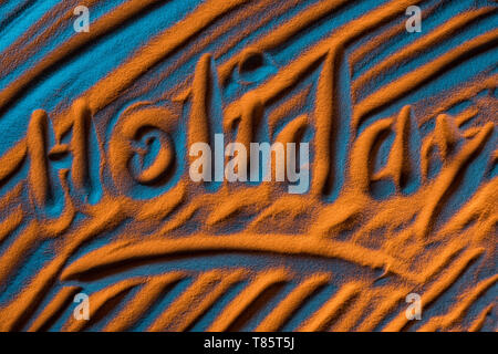 top view of word holiday written in sand with smooth waves and color filter - Stock Photo