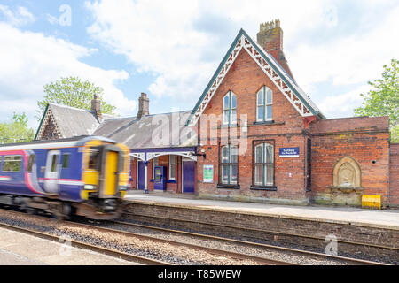 Platform and buildings of Sankey for Penketh Railway Station, West Warrington, Cheshire, England with speeding train passing through - Stock Photo