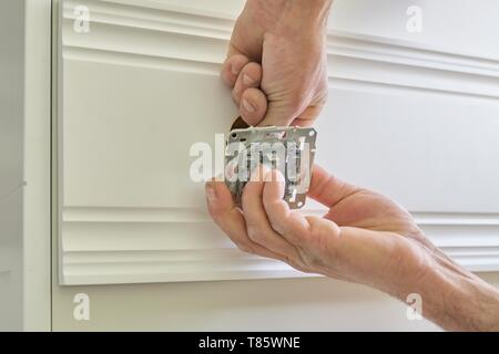 Installation of electrical sockets in wood, closeup of hand of electrician installing wall outlet in wall wooden panel board - Stock Photo