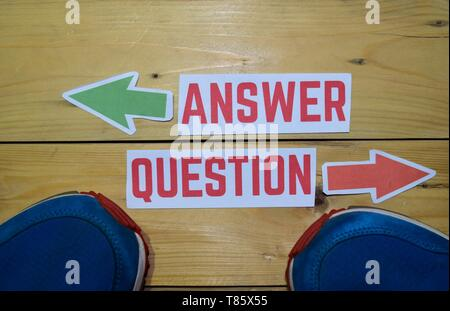 Answer or Question opposite direction signs with sneakers on wooden vintage background. Business, education, finance and concepts - Stock Photo