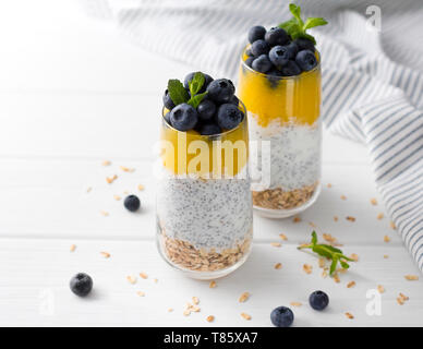 Two Glasses of chia pudding with blueberries, mango mousse and oat granola on the kitchen table.  - Stock Photo