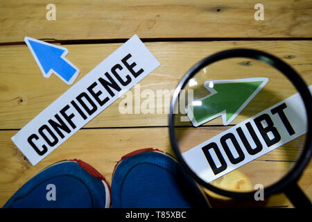 Confidence or Doubt opposite direction signs in magnifying with sneakers and eyeglasses on wooden vintage background. Business and education concepts - Stock Photo