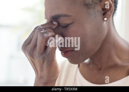 Woman touching bridge of nose