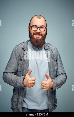 he lifestyle of a successful young man with glasses , beard, fashionable denim jacket showing thumbs up,men's emotional portrait in Studio - Stock Photo