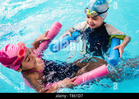 Children playing with water noodles - Stock Photo