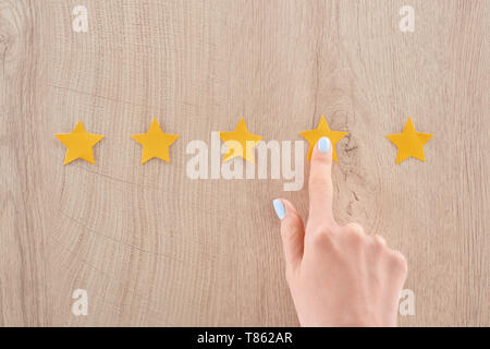 partial view of woman pointing with finger at star on wooden table - Stock Photo