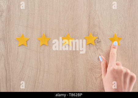 cropped view of woman pointing with finger at star on wooden table - Stock Photo