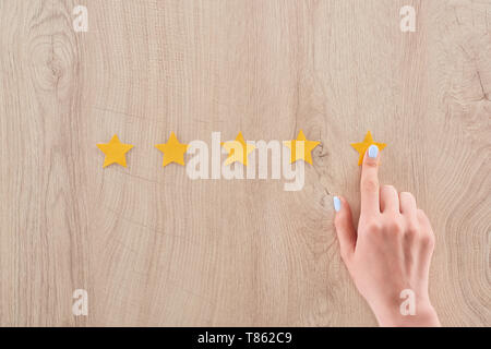 cropped view of woman pointing with finger at yellow star on wooden table - Stock Photo