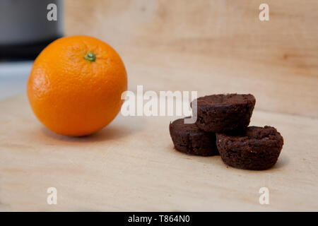 An orange and a small stack of brownies together on a kitchen cutting board - Stock Photo