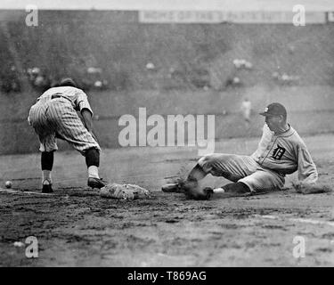 Detroit Tigers player slides safely into third base as a Washington Senators fielder reaches to the left for the ball during a baseball game 1910.